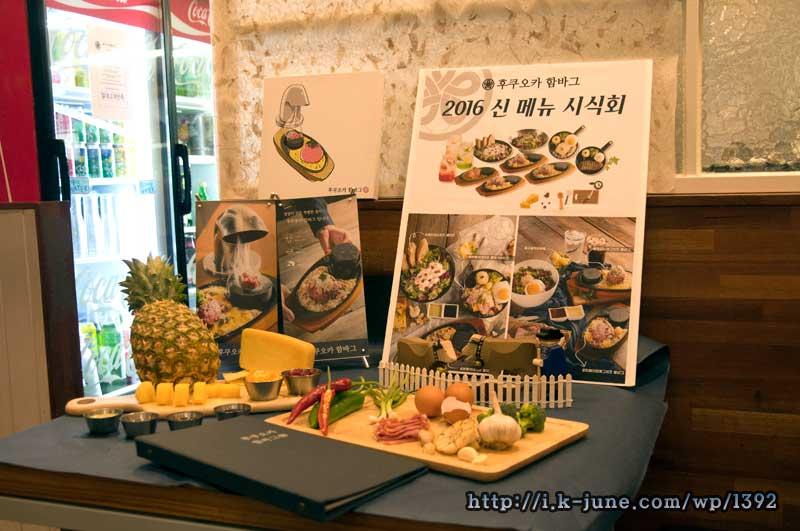 테이블 위에 신메뉴 시식회 포스터와 인조 음식재료들