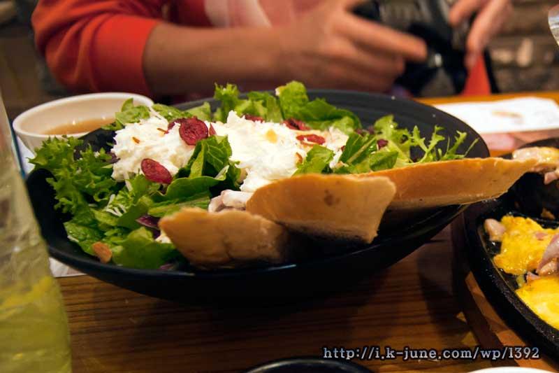 접시위에 샐러드, 치즈, 빵.