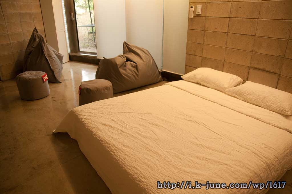 2인용 침대와 대형 쿠션이 있다.