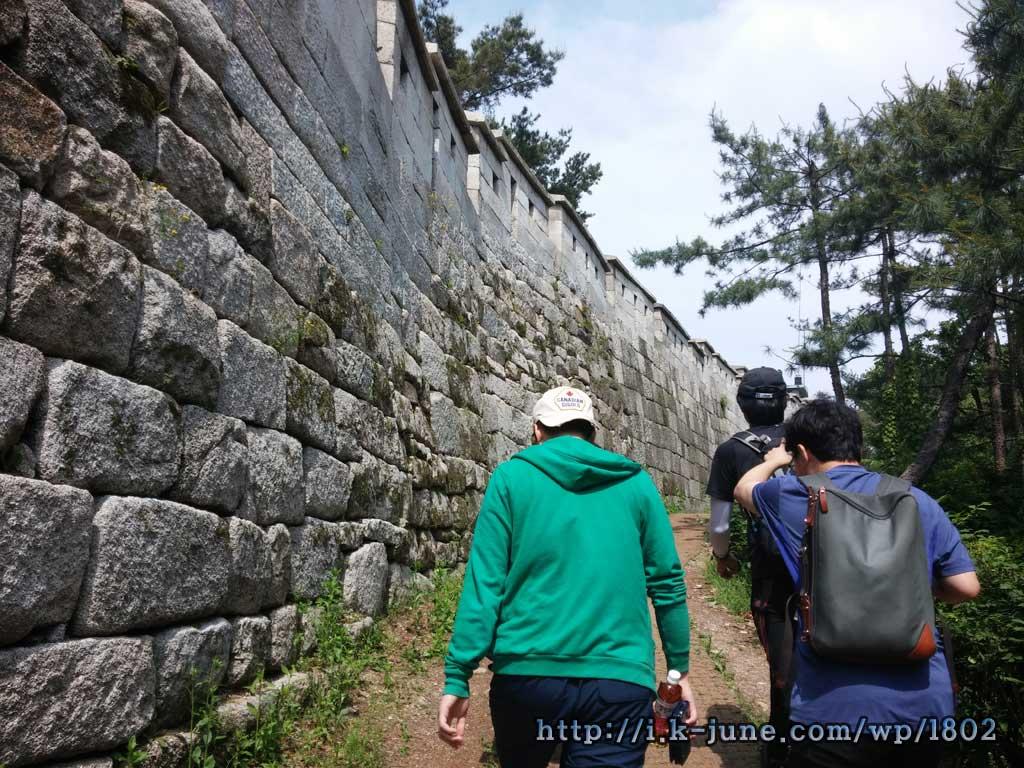 경사가 있는 산길 옆에 성곽이 있다.