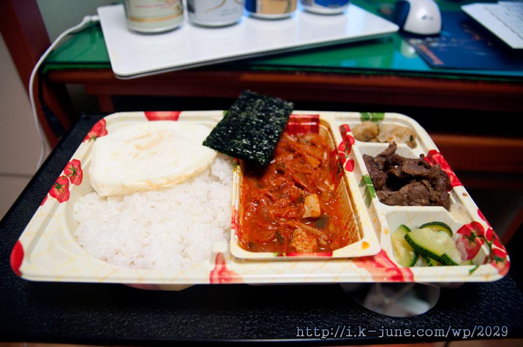 맨 왼쪽에 밥과 계란 후라이, 중간에 김치찌개와 김, 오른쪽 반찬칸은 3칸으로 나위어 있는에 각각 오뎅, 쇠고기, 오이가 있다.