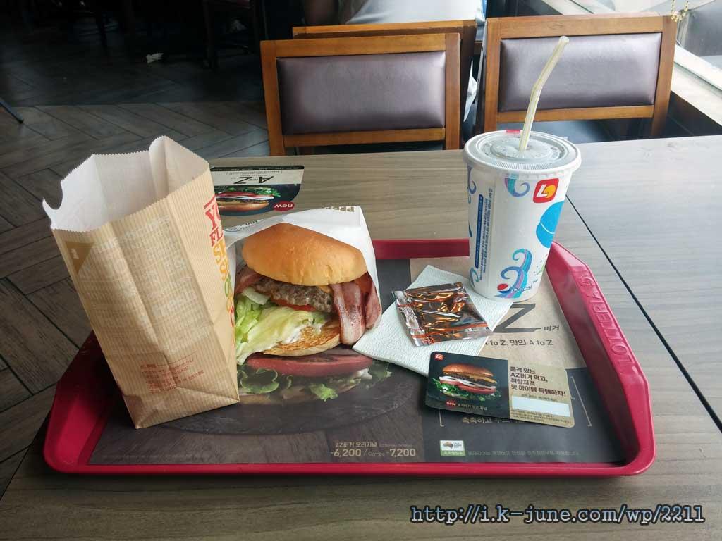 플라스틱 판 위에 올려진 햄버거와 콜라 종이컵의 모습