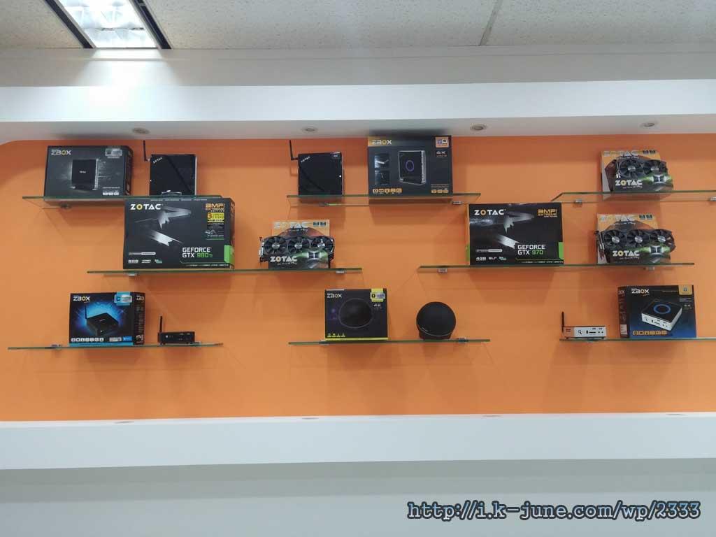 벽 선반에 조텍의 제품들이 진열되어 있다. GTX980Ti, GTX1070, GTX1080등.