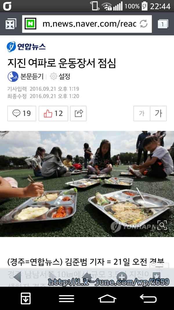 운동장 가운데 식판들이 놓여 있고 초등학생들이 식사를 하고 있다.