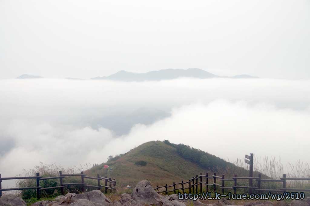 나무가 없는 산 밑에 구름이 깔려 있다.