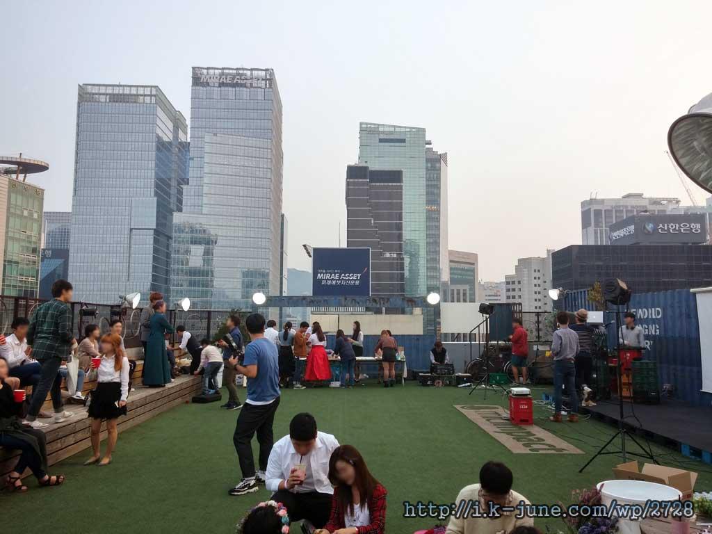푸른 잔디가 깔려있는 옥상의 모습. 멀리 고층빌딩이 보인다.