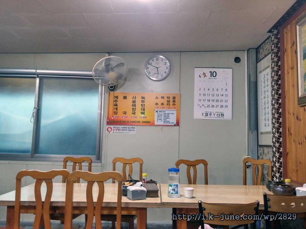 식당 내부에 테이블이 있고, 벽에는 메뉴판이 붙어 있다.