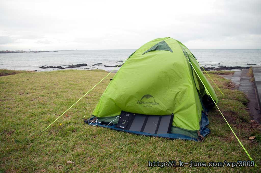 바닷가 잔디밭 위에 텐트가 설치되어 있다.