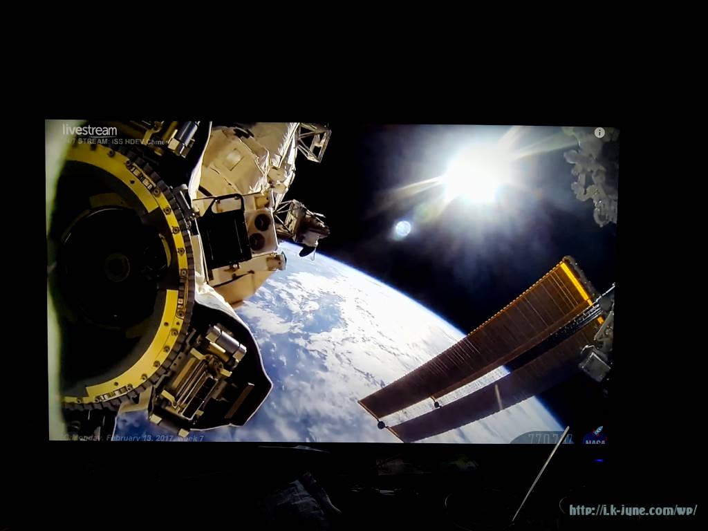 내리쬐는 태양빛과 밑에는 푸른지구가 보이는 우주정거장의 모습