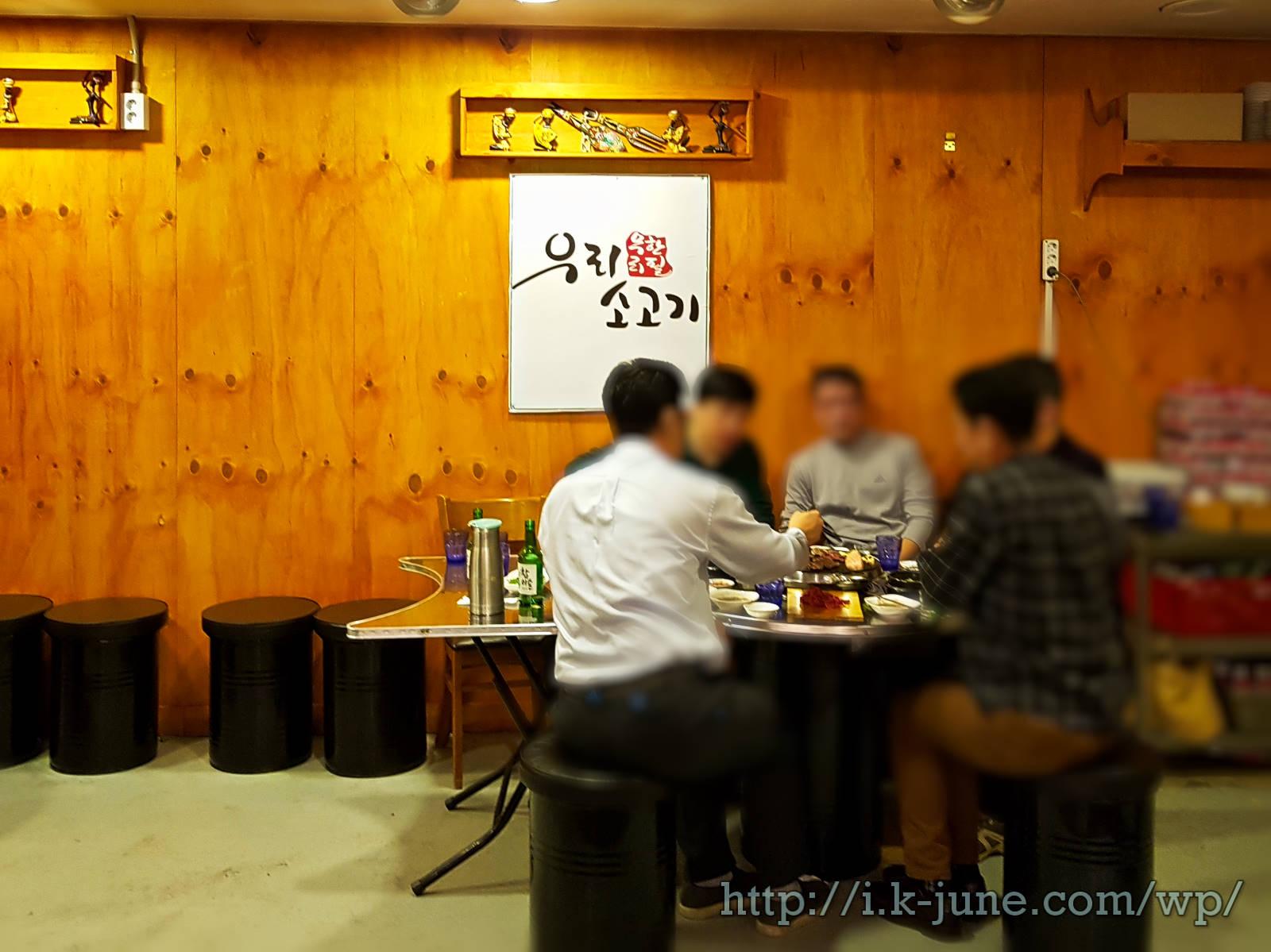 벽에는 우리 무한리필 소고기 하얀색 간판이 있고 테이블에 남자 5명이 앉아 있다.